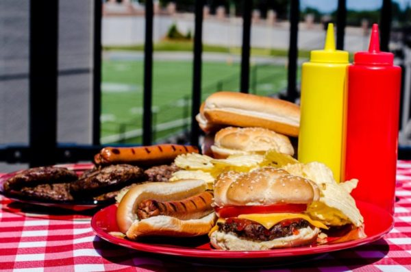 American football pregame party with cheeseburger, hot dog, potato chips, hamburger patties, hot dog wiener, ketchup and mustard bottles and buns. Football field in background.